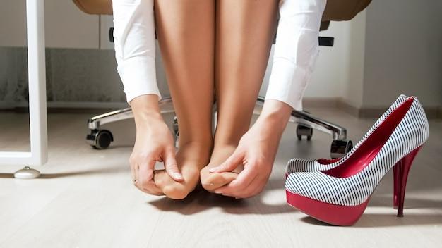 Молодая женщина массируя ноющие ноги и ноги после рабочего дня под офисным столом.