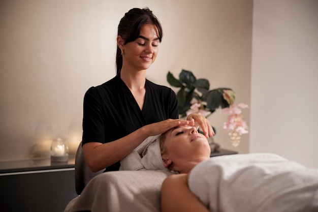 Young woman massaging her client's face