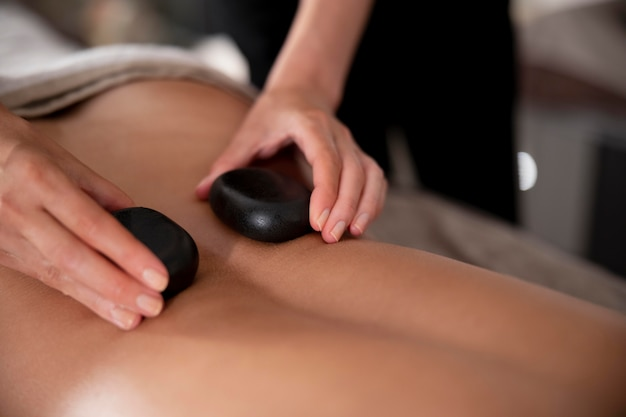 Young woman massaging her client with stones