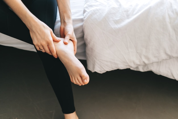 Молодая женщина массирует ногу на белой кровати после тренировки или тяжелого рабочего дня.