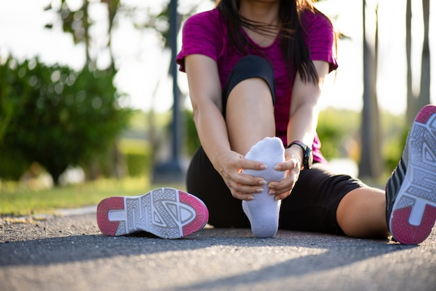 Young woman massaging her painful foot while exercising