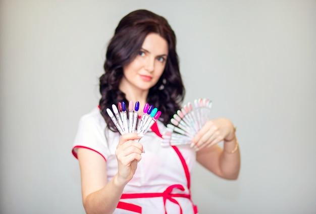 Молодая женщина-мастер маникюра позирует с образцами ногтей. мастер-маникюр держит образец палитры веером. сосредоточьтесь на ногтях