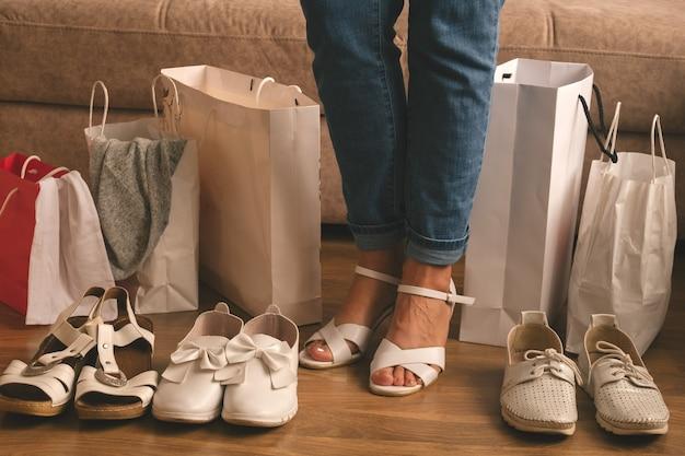 Молодая женщина измеряет новую обувь и стоит между хозяйственными сумками дома, концепция доставки и покупок