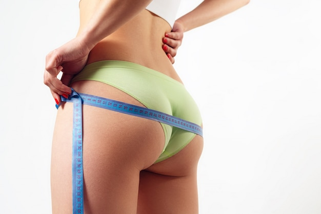 A young woman measures the circumference of her thighs and buttocks with a centimeter tape. on white wall the concept of weight loss, proper nutrition, fitness