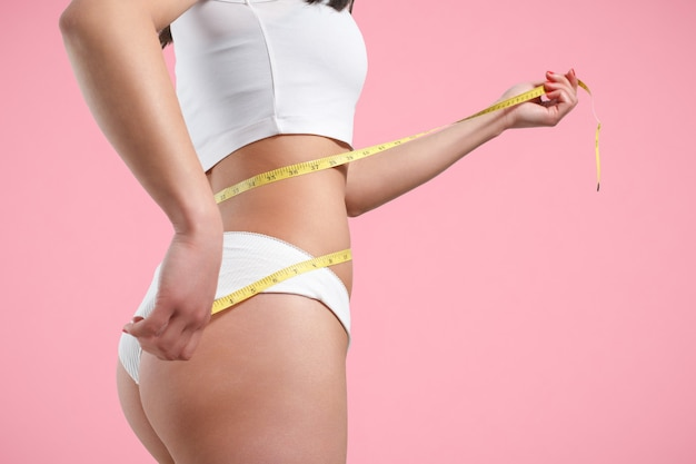 A young woman measures her waist with a measuring tape. on a pink background.