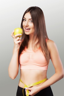 A young woman measures her waist with a tape measure and eats an apple. strict diet. beautiful body.