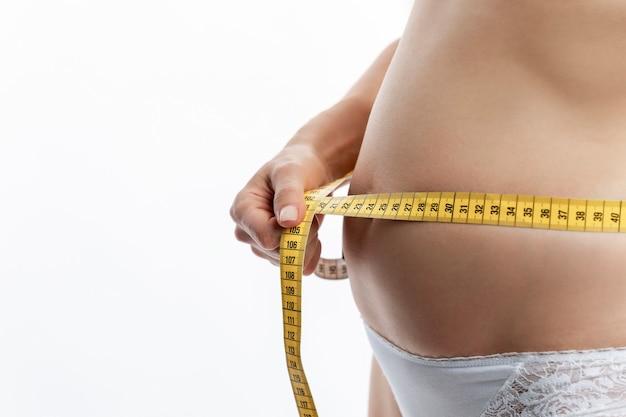 젊은 여성은 테이프로 복부의 부피를 측정합니다. 건강과 적절한 영양. 흰색 배경. 텍스트를 위한 공간입니다.