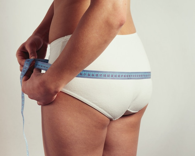 A young woman measures the volume of the buttocks with a measuring tape. on a beige background.