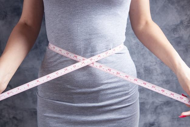 측정 테이프를 가진 배꼽을 측정하는 젊은 여자