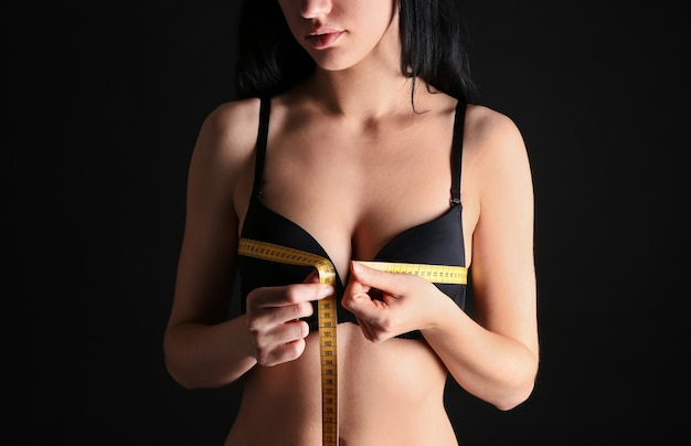 Молодая женщина измеряет грудь на темноте