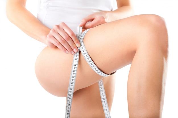 젊은여자가 그녀의 허벅지를 측정