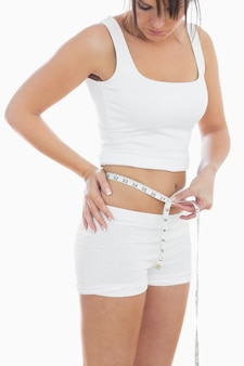 Young woman measuring waist