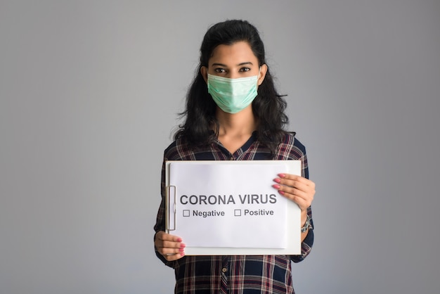 A young woman in a medical mask holding a board of the epidemic of coronavirus, covid-19