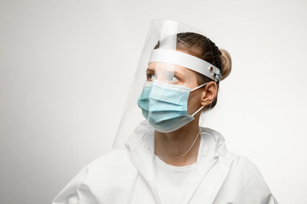Young woman in medical mask and protective shield on her head looking away.
