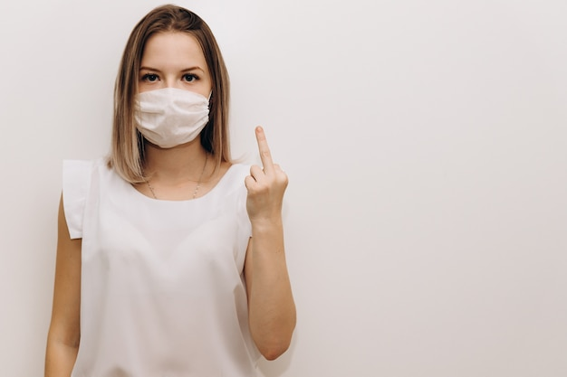 Young woman in a medical mask shows the middle finger