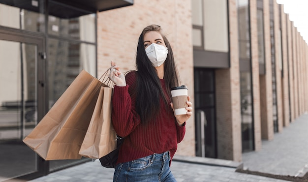 Young woman in medical mask walk outdoors with coffee cup and shopping bags after shopping