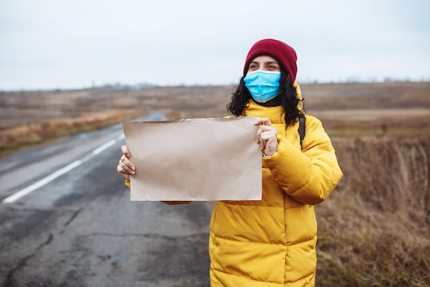Young woman in a medical mask wearing yellow jacket and red hat stands with a poster blank paper on the side of an empty road.
