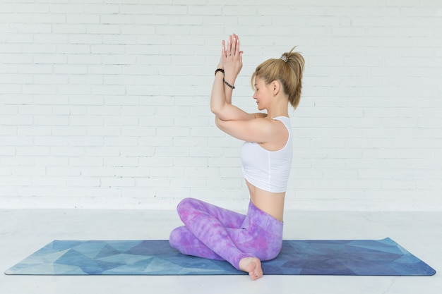 Young woman meditates while practicing yoga