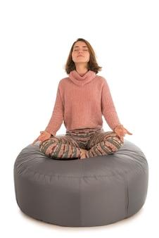 若い女性は白で隔離の丸い形の灰色のお手玉の椅子に蓮華座に座って瞑想します。