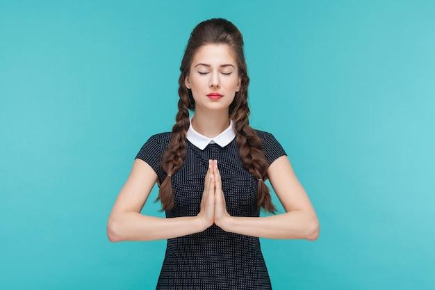 명상을 하고 요가를 하거나 기도하는 젊은 여성. 파란색 배경에 실내, 스튜디오 촬영
