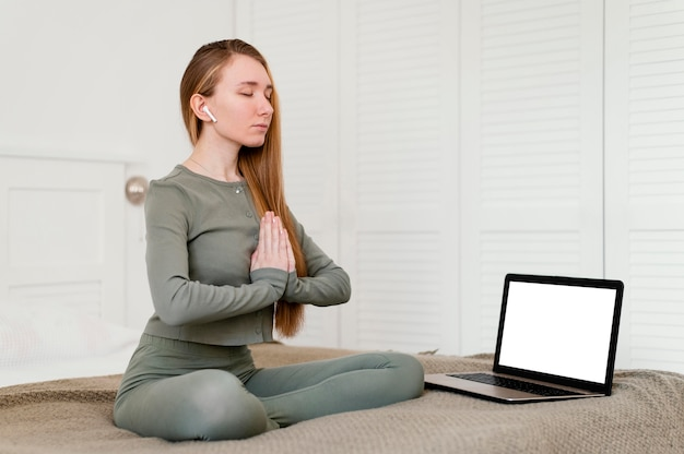 横にラップトップで自宅で瞑想する若い女性