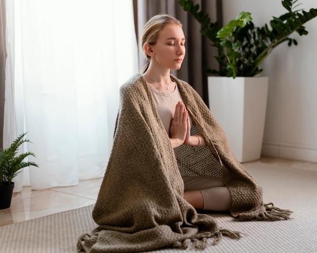 家で瞑想する若い女性
