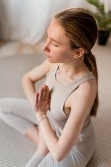 Молодая женщина медитирует дома