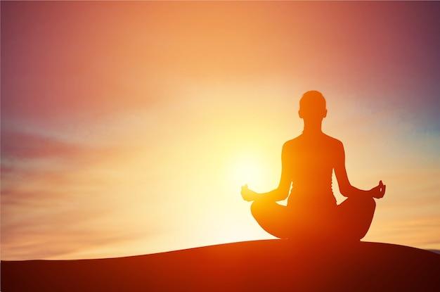 美しい夕日に面した山頂から瞑想する若い女性。健康な心と体。