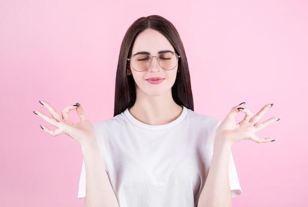 명상, 요가 제스처에 그녀의 손을 잡고 젊은 여자, 핑크 스튜디오 배경에 고립, 닫힌 눈