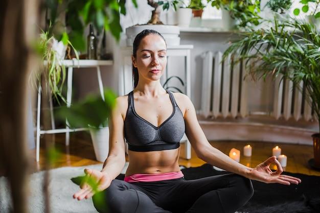 Giovane donna che medita a casa
