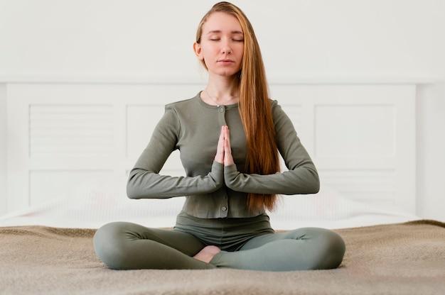 Giovane donna meditando a casa