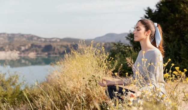 Молодая женщина медитирует на природе