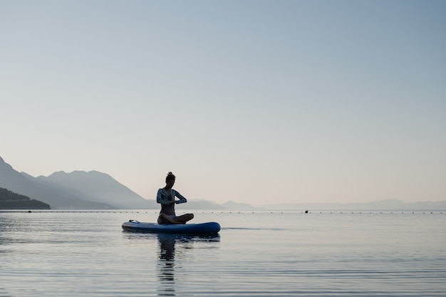 Young woman meditating in lotus position with her hand joined in front of her chest, sitting on sup board floating on calm morning water.