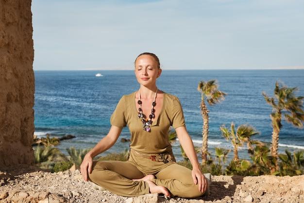 Молодая женщина, медитируя у моря