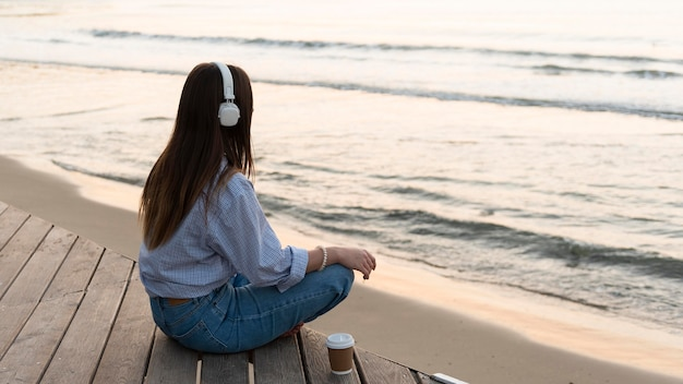Молодая женщина медитирует рядом с морем в наушниках
