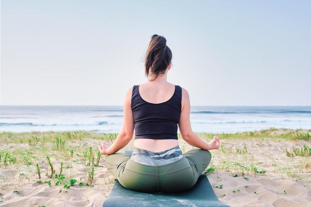ビーチで瞑想する若い女性