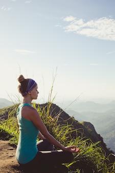산 꼭대기에서 명상하는 젊은 여자