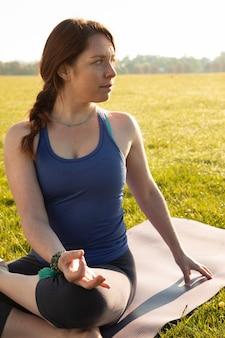 Young woman meditating outdoors on yoga mat