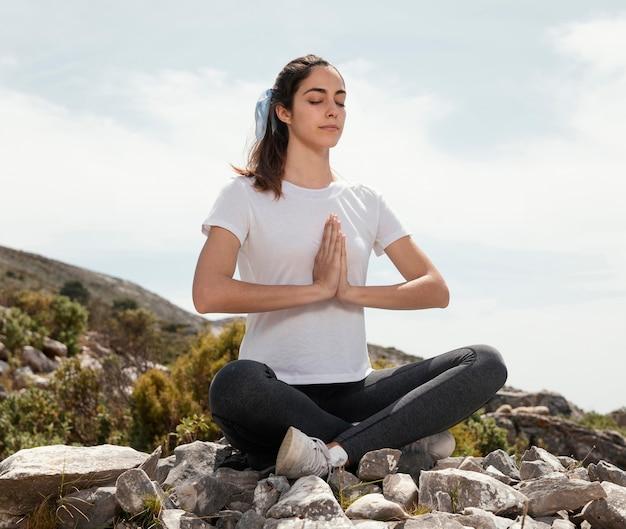 Молодая женщина медитирует на открытом воздухе