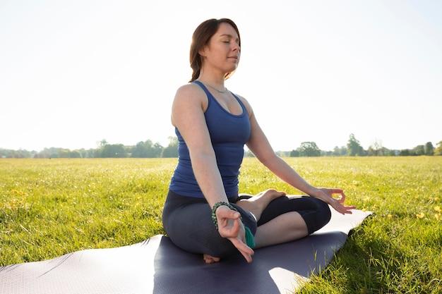 Giovane donna che medita all'aperto