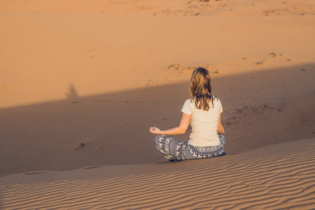 Young woman meditating in rad sandy desert at sunset or dawn