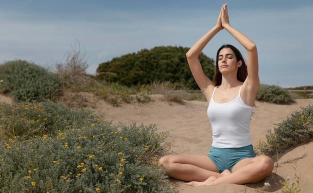 Giovane donna che medita sulla sabbia