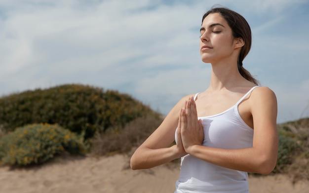 Young woman meditating on sand
