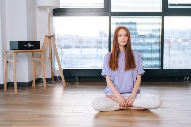若い女性は、事務室の窓の背景に蓮華座の床に座って瞑想します。