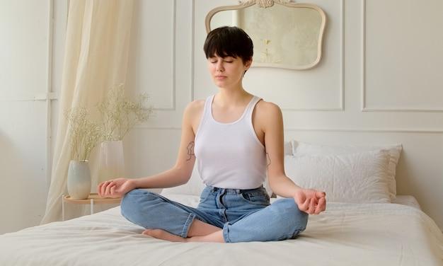 Молодая женщина медитирует, сидя дома, спокойная женщина, глубоко вздыхая и расслабляясь