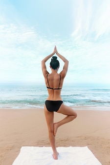 Young woman meditation in a yoga pose at the beach. girl practices yoga
