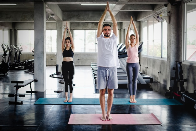 Young woman and men training lifestyle healthy body workout in gym, sports style yoga concept