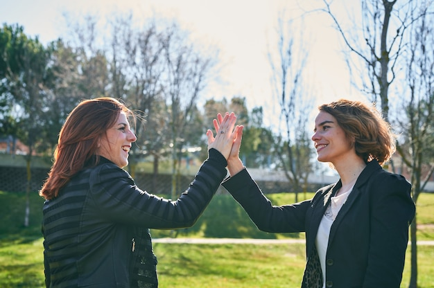 Young woman and a middle-aged business woman high-fiving looking into each other's eyes with a big smile.