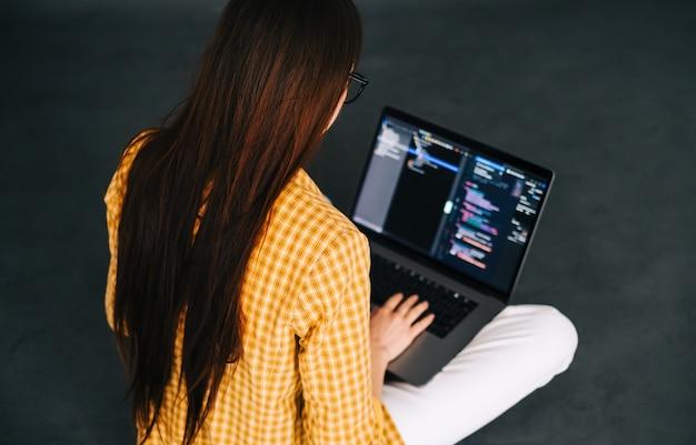 若い女性のモバイル開発者は、コンピューター、プログラマーの仕事でプログラムコードを書きます。