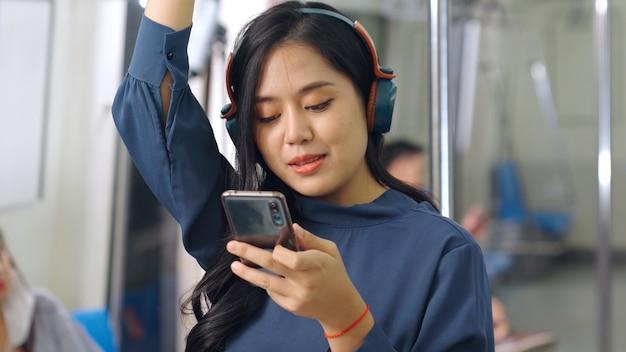 Мобильный телефон молодой женщины на общественном поезде. городской городской образ жизни коммутирующих концепции.